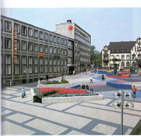 Hajek, Otto Herbert: Brunnen mit Platzgestaltung/ Synagogenplatz (damals: Viktoriaplatz), Blick von der Schloßstraße auf ehem. Sparkasse (dort seit 2009: MedienHaus), © VG Bild-Kunst, Bonn 2019; Foto: Kunstmuseum Mülheim an der Ruhr 1985.