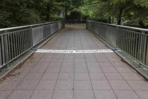 Nekes, Werner: Kegelanamorphosen, Schirftzug auf der Kfar-Saba-Brücke, Zustand 2020; Foto: Kunstmuseum Mülheim an der Ruhr/ Ralf Raßloff, Copyright VG Bild-Kunst 2020.
