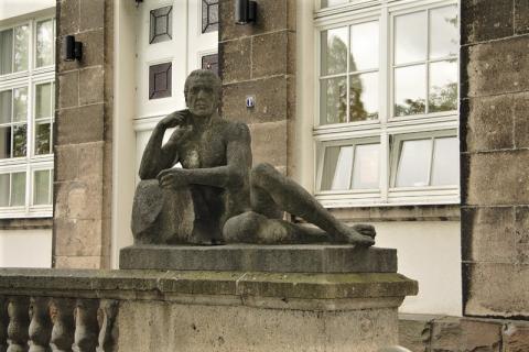 """Janssen, Ulfert: Liegefigur an Treppe, Haupteingang Max-Planck-Institut, """"Geistige Arbeit""""; Foto: Kunstmuseum Mülheim an der Ruhr 2016."""