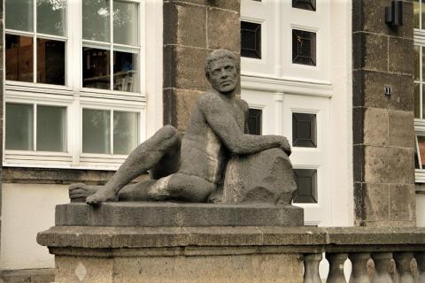 """Janssen, Ulfert: Liegefigur an Treppe, Haupteingang Max-Planck-Institut, """"Körperliche Arbeit""""; Foto: Kunstmuseum Mülheim an der Ruhr 2016."""