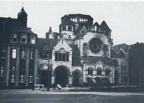 Janssen, Ulfert: Skulpturgruppe über dem Portal der Sparkasse mit ausgebrannter Synagoge (Zustand nach 1938), Foto: Mülheimer Jahrbuch 1984.